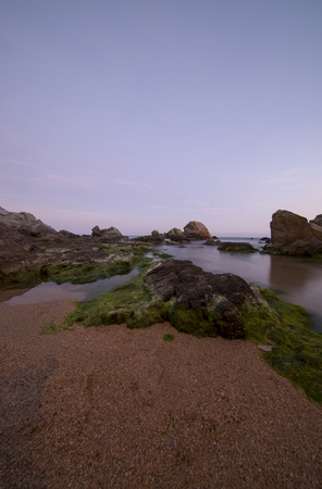 Beach and rocks at sunset in Lloret de Mar, Spain 스톡 콘텐츠