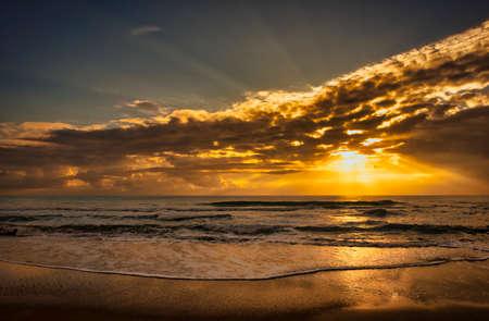 The sunrise sun through the clouds on the beach, Spain