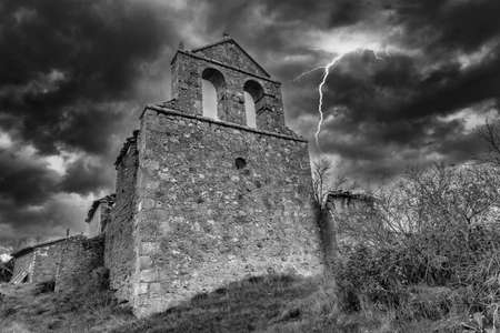 An abandoned hermitage in black and white under a storm, Spain