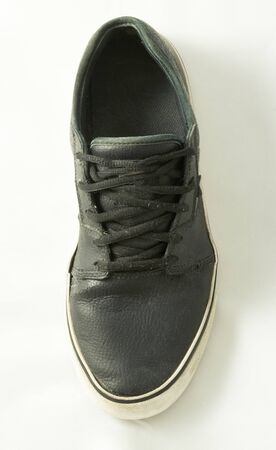 A black casual sneaker with a white sole.