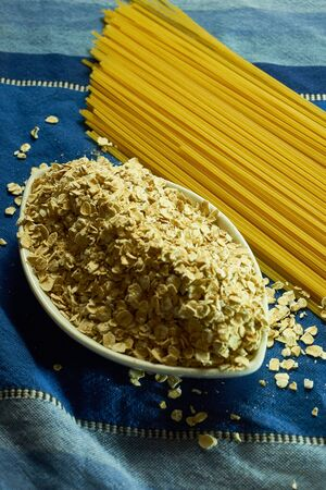 A bunch of raw spaghetti next to a bowl of oatmeal. The set is located on top of a blue fabric.