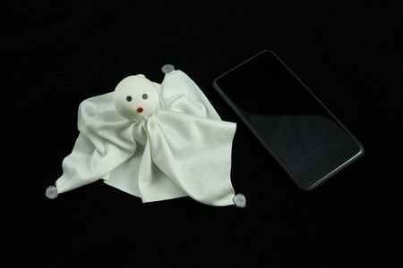 A ghost of white cloth next to a mobile phone. The background is black. The image is taken from above. Communication concept.