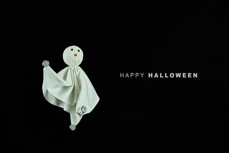 A white cloth ghost next to a happy halloween lyrics. The background is black. Party concept.