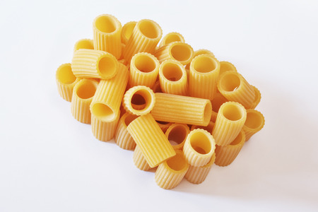 Italian pasta called mezzi rigatoni on a  white background ,tube-shaped pasta with ridges down their lenght , studio shot ,