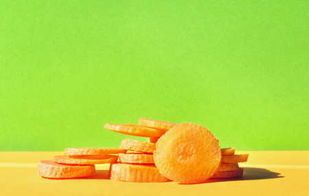 Slices of carrot on a colored background, studio shot, green and orange colors in perfect harmony, vibrant colors, front view