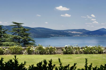 Glimpse of Lake Bracciano in a bright sunny day , in the foreground a beautiful garden with flowers ,in the background mountains