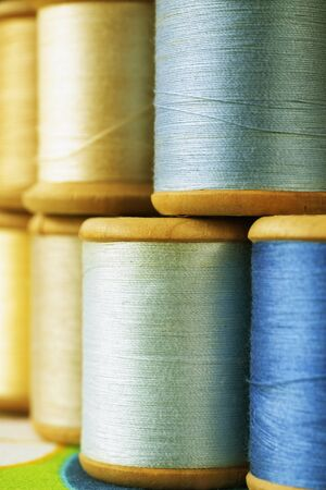 Different wooden spools of colored thread on  colored background , different shades of blue and yellow color  in every spool Stock Photo