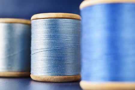 Three wooden spools of colored thread on  colored background , different shades of blue color  in every spool