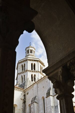 Beautiful bell tower of Cistercian abbey of Fossanova -Italy - in the foreground part of columns of the cloister                               Stock Photo