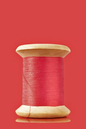 A wooden spool of red thread on  colored background