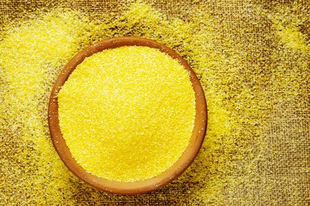 Yellow grains of cornmeal  on bowl  ,it's a common staple food  of Northen Italian called polenta