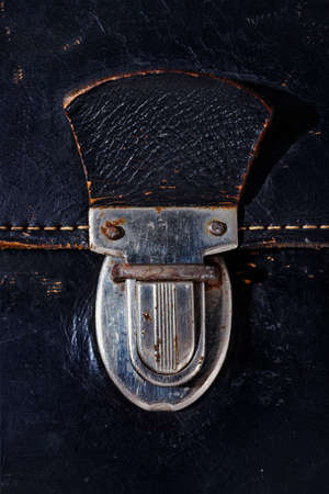 Detal of old metal bag press push lock, old black leather bag with yellow thread, rusty metal
