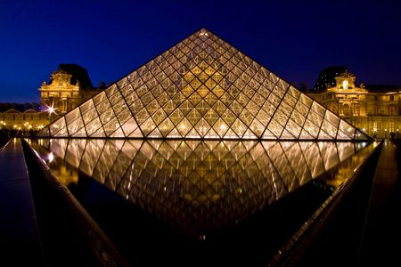 tourist destinations: Paris France APR 16,2010 - Reflection of Louvre pyramid shines at dusk during the Summer Exhibition in Paris. This is one of the most popular tourist destinations in France.