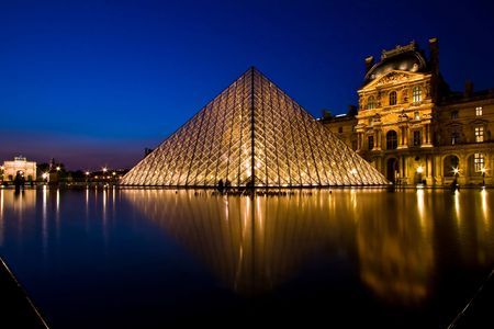 famous place: Paris France APR 16,2010: Reflection of Louvre pyramid shines at dusk during the Summer Exhibition in Paris. This is one of the most popular tourist destinations in France.