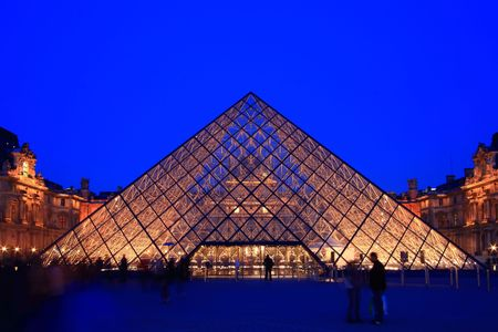 louvre pyramid: Paris France APR 16,2010: Entrance of Louvre pyramid shines at dusk during the Summer Exhibition in Paris. This is one of the most popular tourist destinations in France.
