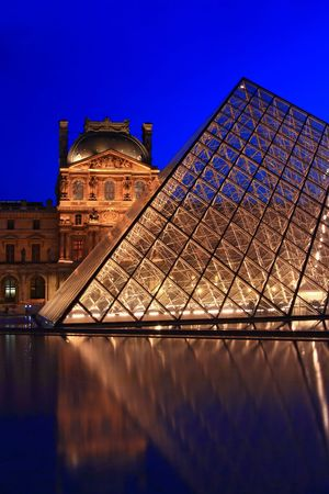 tourist destinations: Paris France APR 16,2010: Closeup of Louvre pyramid shines at dusk during the Summer Exhibition in Paris. This is one of the most popular tourist destinations in France.