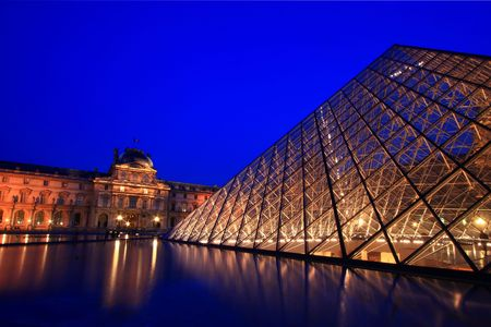 Paris France APR 16,2010: Closeup of Louvre Pyramid shines at dusk during the Summer Exhibition in Paris. This is one of the most popular tourist destinations in France.