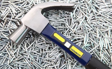Hammer on heap of  Silver Concrete nails Stock Photo - 8021069