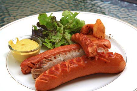 comida alemana: Apetecibles salchichas a la plancha con ensalada verde y salsa de mostaza