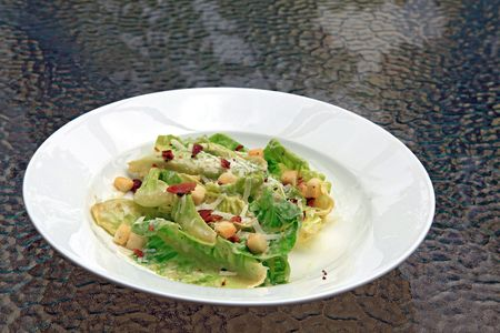 ceasar salad in white dish on glass table photo
