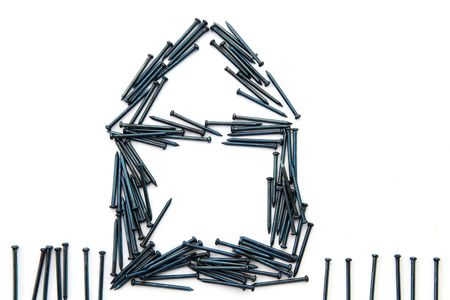 Conceptual of blue steel nails construct house with fence Stock Photo - 8021997