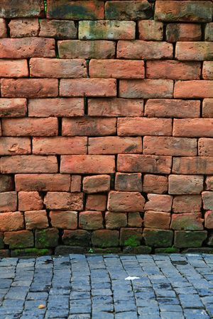 irregular shapes: irregular shapes of red stone brick wall with pavement, vertical Stock Photo