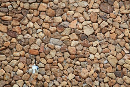 Traditional Stone Brick Wall made of fragment stones in irregular shapes with lamppost photo