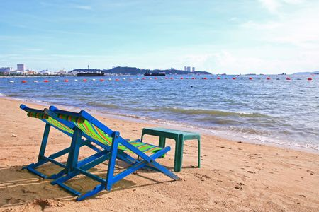 Couple of beach chairs and table on the beach in Pattaya City Stock Photo - 8089703