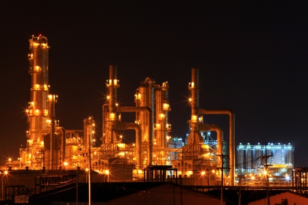 oil refinery: scenic of petrochemical oil refinery plant shines at night, closeup Stock Photo