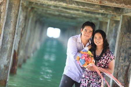 couple standing outdoors smiling under pier on the beach photo