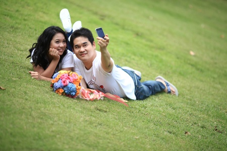 ypung couple laying on grass and taking self portrait with mobile phone Stock Photo - 8257846