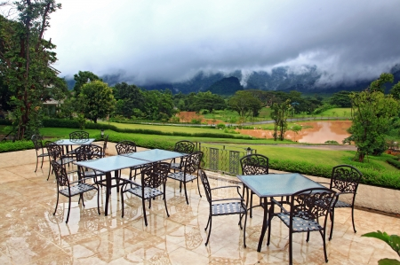breakfast garden: beautiful view of restaurant surround by mist lake and mountains with empty table Stock Photo