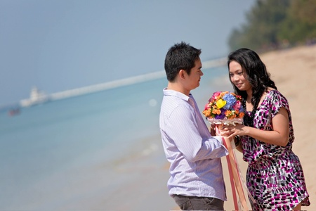 attractive handsome young man giving flowers to his pretty girlfriend photo