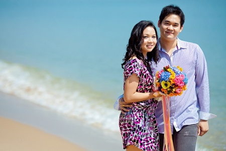 attractive couple standing together in the beach with beautiful bouquet photo