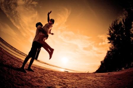 siluetas de enamorados: Escena rom�ntica de las parejas en la playa