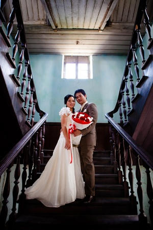 Bride and groom standing at ladder indoor of old building photo
