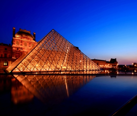 PARIS - APRIL 16, 2010: Closeup of Louvre Pyramid shines at dusk during the Summer Exhibition in Paris. Louvre is the biggest Museum in Paris displayed over 60,000 square meters of exhibition space.