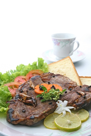 t bone: closeup of T Bone Pepper Steak dressing by vegetable and bread  with Coffee cup