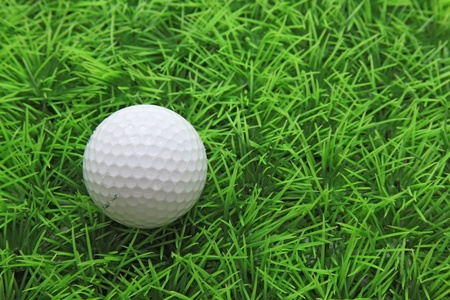 closeup of golf ball on green grass photo