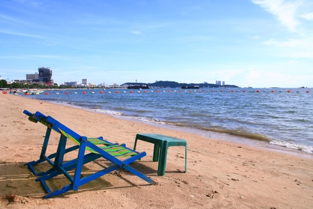 Couple of beach chairs and table on the beach in Pattaya City photo