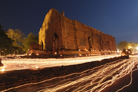 candle light trail of Buddhism Ceremony at temple ruin at dusk on Asalha Puja day photo