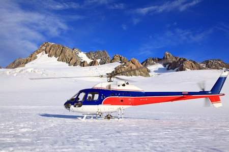 Helicopter landing on top of Franz Josef Glacier in New Zealand.