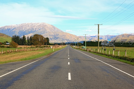 Long road stretching out into the distance with snow mountain background in New Zealand photo