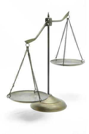 justicia: desequilibrio de escalas de bronce dorado de Justicia sobre la perspectiva frontal blanca Foto de archivo
