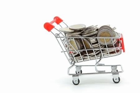 ganancias: carro de compras aislada con monedas de plena riqueza interior sobre fondo blanco
