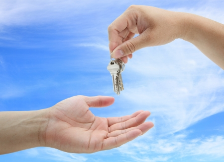man handing over the set of keys house against blue sky photo