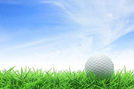 golf ball op groen gras tegen blauwe hemel