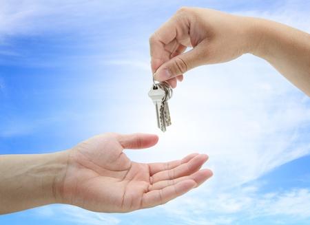 hand giving set of house keys against blue sky and sun photo
