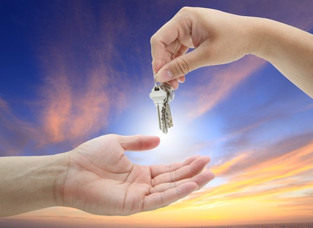 hand giving set of house keys against with twilight background photo
