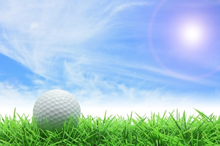 golf ball on green grass over sunny blue sky photo